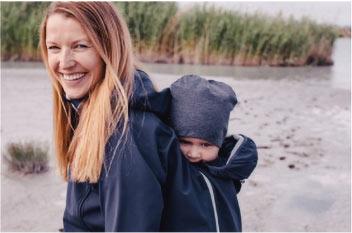 Mutter geht mit Kind auf dem Rücken spazieren